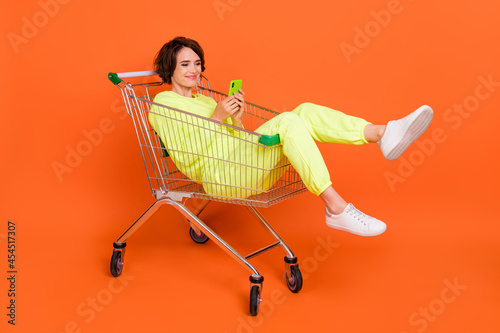 Foto Portrait of attractive cheery funny focused girl sitting in shopping cart chatti