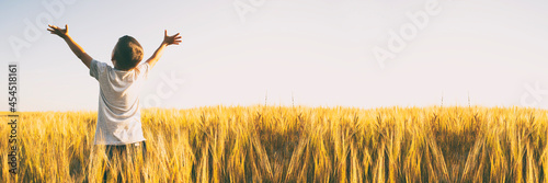 Fotografie, Obraz Boy raised his hands in the middle of the wheat field