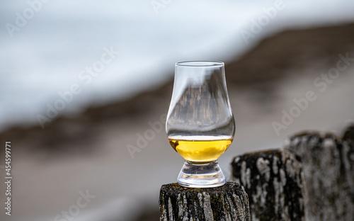 Obraz na plátně Tasting of dram single malt scotch whisky on seashore in Scotland, old wooden po