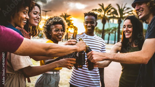 Fotografie, Obraz Group of multiethnic happy friends having party outside celebrating toasting bee