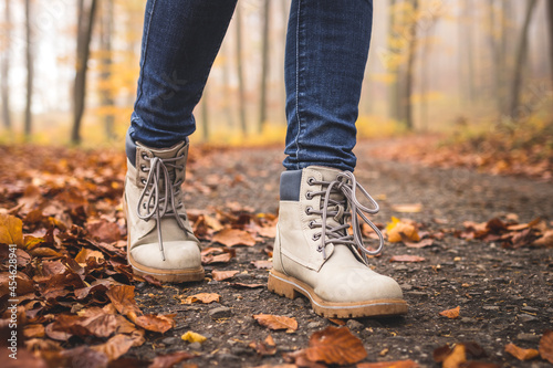 Walking with hiking boots on road at autumn woodland Fototapet