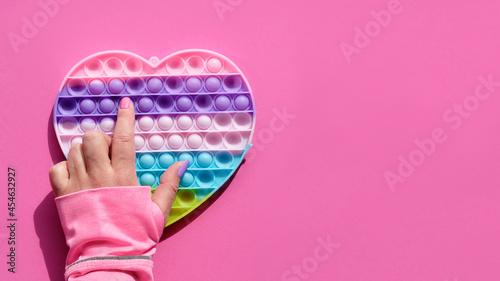 Obraz na płótnie Heart shaped pope it antistress toy with female hand