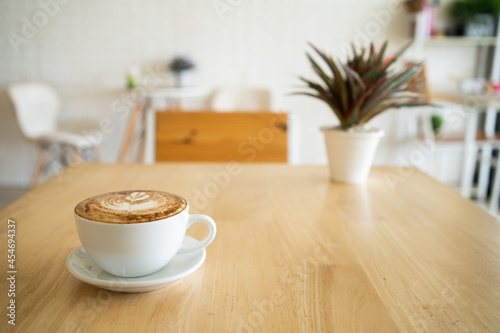Murais de parede A hot cappuccino mug with latte art on top placed on a wooden table in a cafe