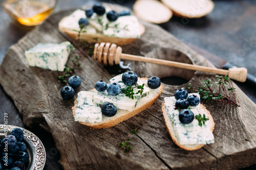 Obraz na plátně Bruschetta with cheese, blueberries and honey on a wooden background