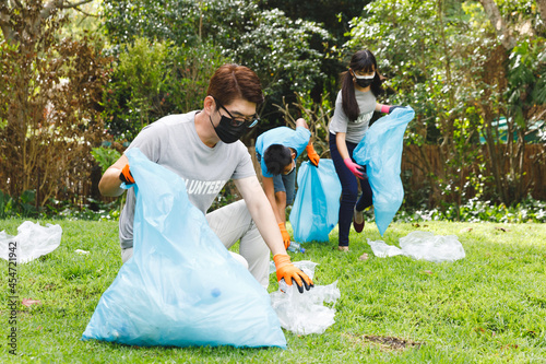 Fototapeta premium Asian parents, son and daughter in face masks putting rubbish in refuse sacks in the countryside