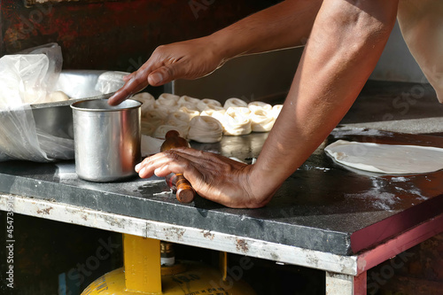 Fotografie, Obraz Process of baking paste on a black table by male baker hands