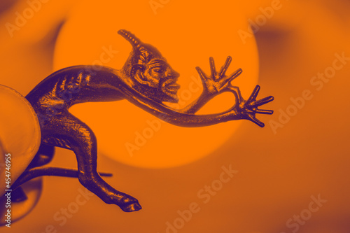 Fotografering A small metal sculpture of the devil with a tail showing his tongue