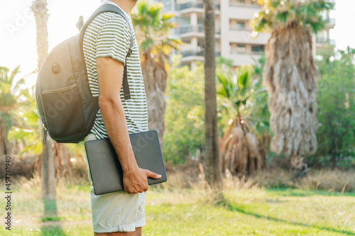 Obraz na plátně Unrecognizable young white man with a backpack holding a laptop with a park in t