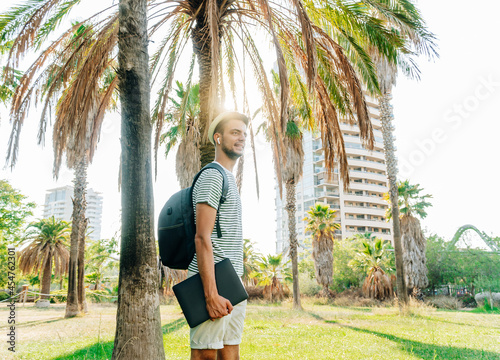Fotografie, Obraz Young white digital nomad standing in a park with a city in the background