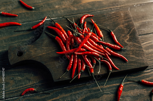 Fotografie, Obraz Chili peppers on a dark wooden board
