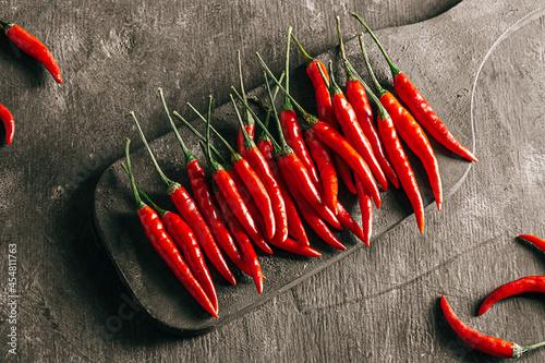 Fototapeta Chili peppers on a dark board