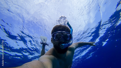 Fotografie, Obraz a man is engaged in snorkeling diving into the depths of the red sea in a mask a