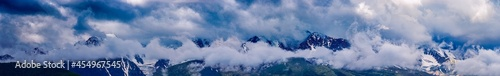 Fotografie, Obraz Panoramic view of plain among hills and mountains under white fluffy clouds in b