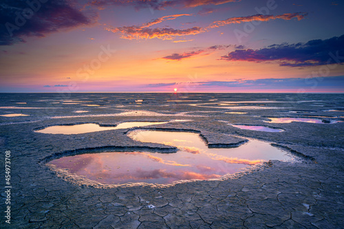 Fotografia Low tide in mudfltas and sunset at the waddensea