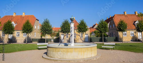 Fotografie, Obraz Panorama of the fountain and old houses in Christiansfeld, Denmark