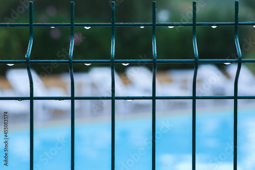 Fotografiet Close-up of a fence wet from the rain, in the background, out of focus, deck chairs and swimming pool