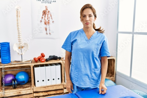 Fototapeta Middle age hispanic physiotherapist woman working at pain recovery clinic skeptic and nervous, frowning upset because of problem