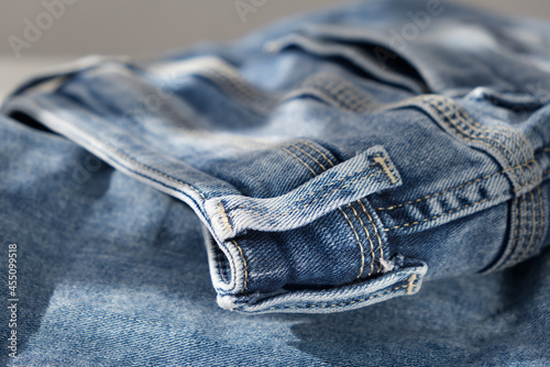 Fotografie, Tablou a blue light jeans on a grey background. Close up. Sunlight