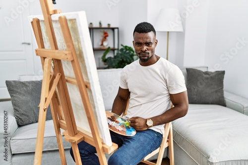 Fotografie, Obraz Young african man painting on canvas at home skeptic and nervous, frowning upset because of problem