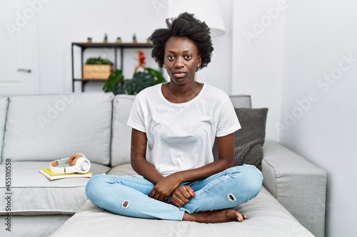 Obraz na plátně African young woman sitting on the sofa at home skeptic and nervous, frowning upset because of problem