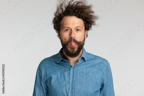 Photo goofy young bearded man sticking out tongue and making silly faces