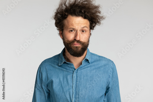 Photo casual relaxed young man with curly hair making funny faces