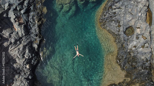 Canvastavla Persona nadando en una cala de mar con agua azul rodeado de rocas