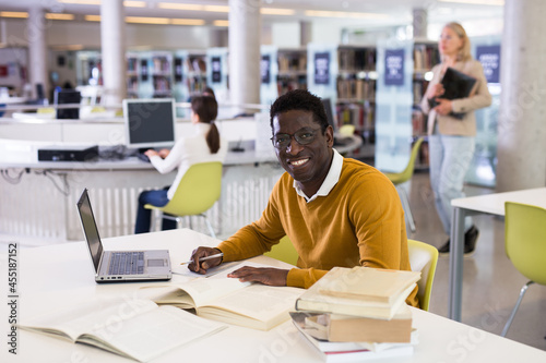 Fotografia Portrait of smiling african-american male student with laptop and book in public library