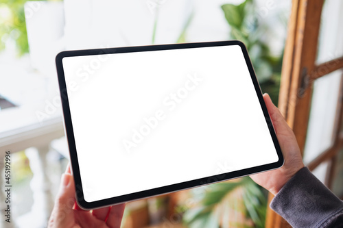 Fotografie, Obraz Mockup image of a woman holding and using digital tablet with blank white deskto