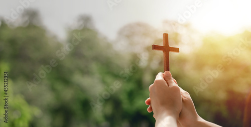 Leinwand Poster girl holding a cross to pray thank god Praise the Lord with outdoor background,