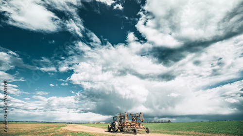 Fotografie, Obraz Tractor With Attached Harrow In Sunny Spring Day