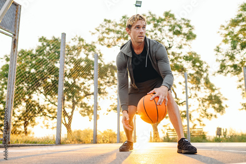 Fototapeta Young cool sunlit concentrated sporty sportsman man wear sports clothes doing ha