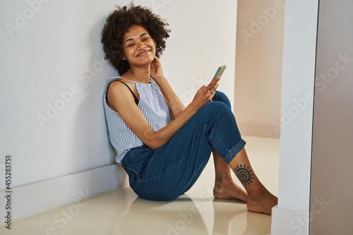 Fotografija Barefoot joyful curly-headed woman leaned back against the wall