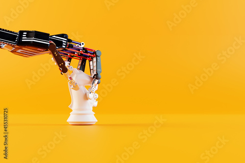 Fotografia Robot hand plays chess and makes a knight move on a yellow background