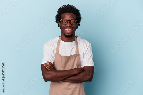 Foto Young african american store clerk isolated on blue background laughing and having fun