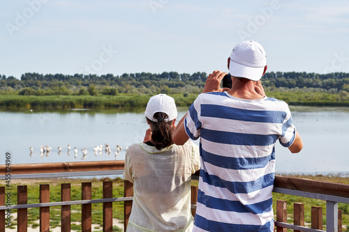 A man and a woman observe and photograph pelicans in the lake from the observation deck Fototapeta