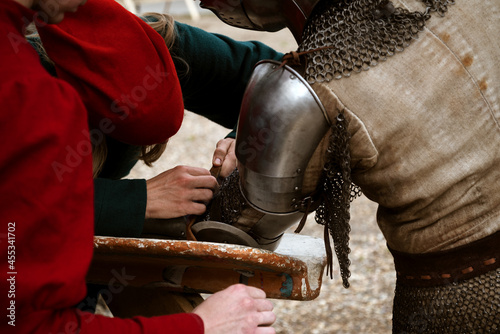 Murais de parede Squires help the knight to attach the shield to the armor on his arm before the battle