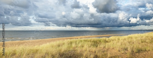 Fotografiet Blue sky with lots of cumulus clouds above the Baltic sea after thunderstorm at sunset