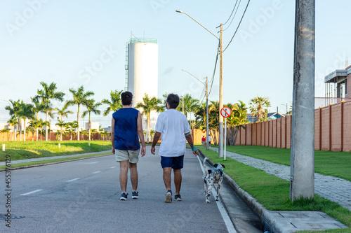 Canvas Print Homens caminham com cão Dalmata ao entardecer