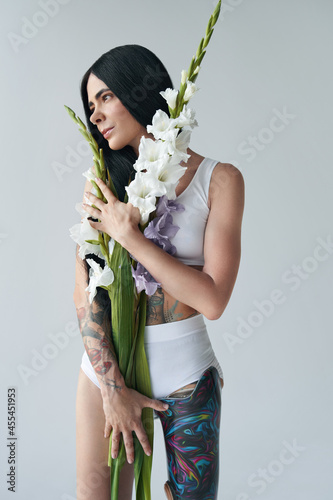 Canvas Print Woman posing with gladioli flowers at the studio with white background