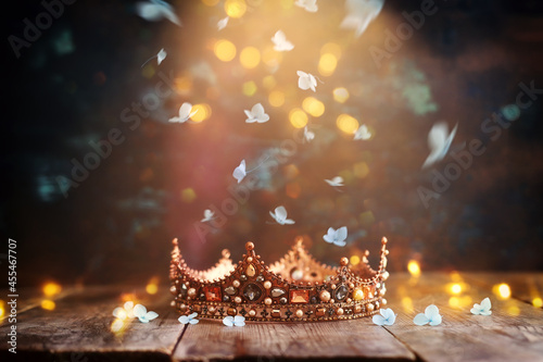 Obraz na plátně low key image of beautiful queen or king crown over wooden old table and falling flowers