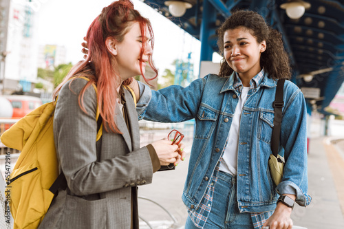 Foto Multiracial two women crying while saying goodbye at train station