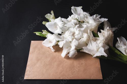 Photo bouquet of white gladioli on black background with envelope