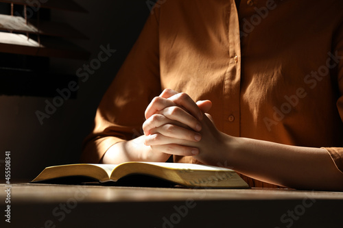 Religious woman praying over Bible at wooden table indoors, closeup