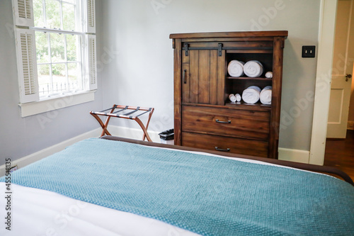Tablou Canvas A simple dark wood stained armoire for storage in a guest bedroom with clean white rolled and organized towels for guests
