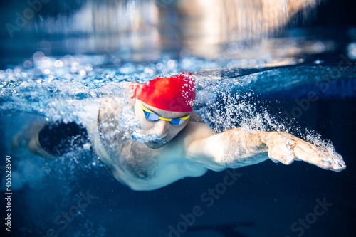 Fototapeta premium One male swimmer practicing and training at pool, indoors. Underwater view of swimming movements details. Healthy lifestyle, power, energy, sports movement concept.