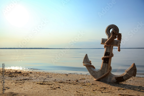 Foto Wooden anchor on river shore near water