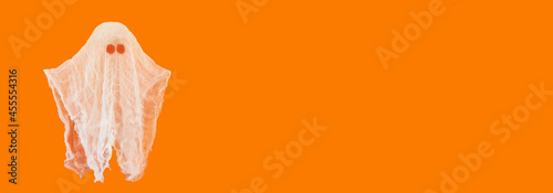 cute white ghost made of fabric on orange background with copy space. halloween decorations concept.