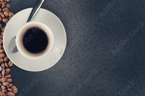 Black hot coffee with foam in a white ceramic cup with coffee beans Fototapet