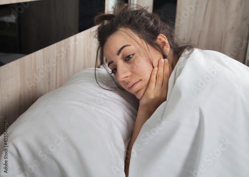 Fotografia Sad woman is lying alone in bed.